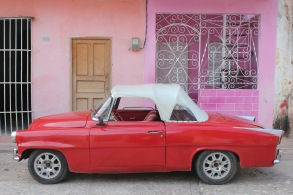 Classic red car in front of a pink wall, Trinidad