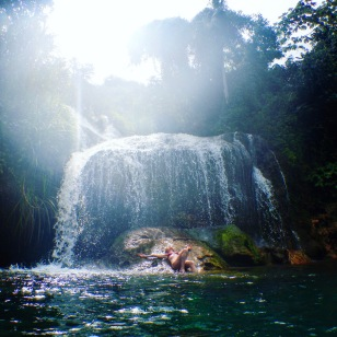 Girl under a waterfall in a natural pool at El Nicho Cuba