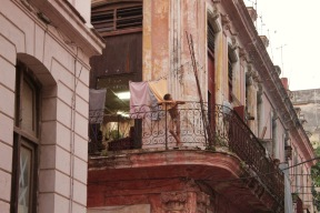 Boy leaning on a balcony in Havana