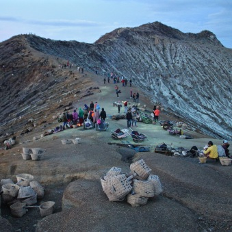 Tourists and sulphur miners on the lip of Kawah Ijen