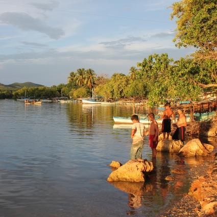 Kids fishing and fishing boats in La Boca near Trinidad