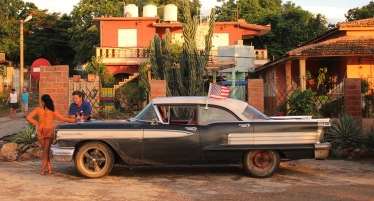 Classic car taxi with American flag in La Boca, Cuba