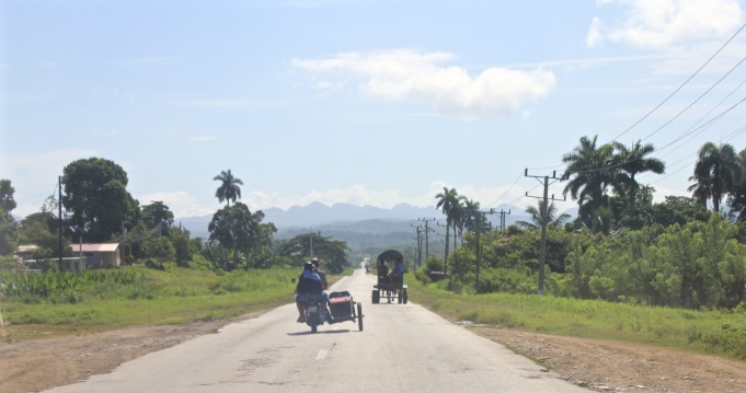 Motorcycle with sidecar and horse carriage on a Cuban road