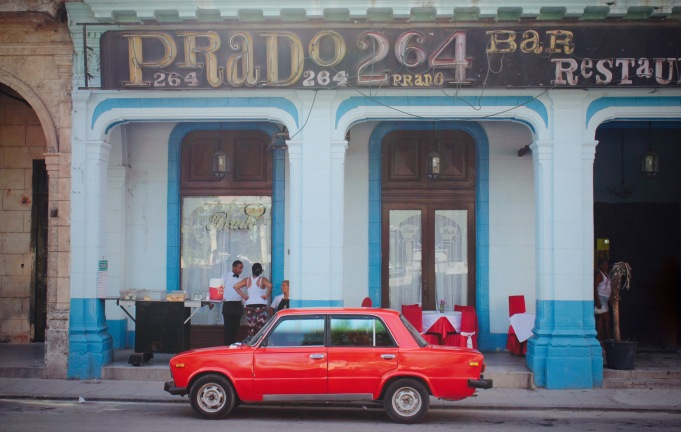 Red car parked in front of a restaurant on the Paseo de Prado, Havana