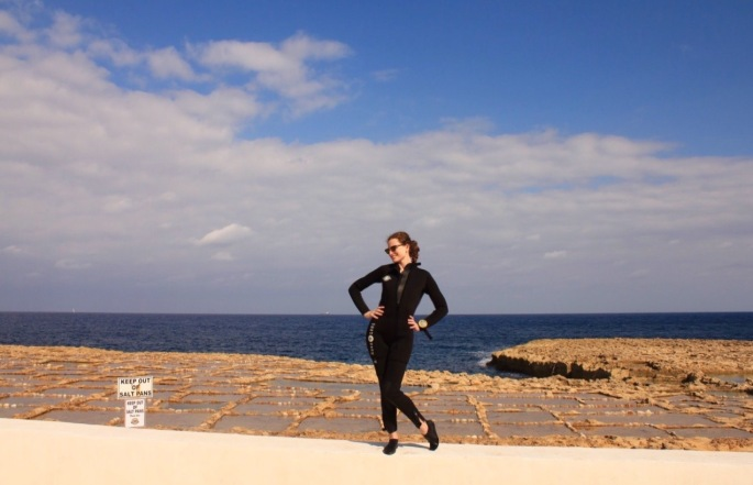 Girl in wetsuit in front of the salt pans near Marsalforn Gozo