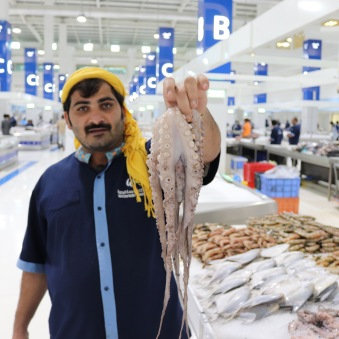 Fishmonger with octopus, new Deira fish souk Dubai