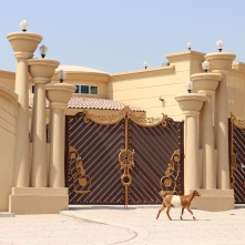 Goat in front of the elaborate entrance to an Emirati villa in RAK