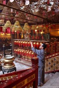 Caretaker hanging up incense coils in Man Mo Temple Hong Kong