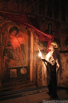 Ethiopian priest showing the church frescoes by candlelight
