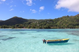 Boat in the turquoise waters of Anse Volbert, Praslin Seychelles