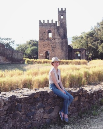 Sofie sitting on a wall in the Royal Enclosure, Gondar